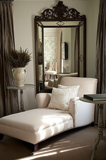 Large mirror behind chaise in a corner of the room makes for a very intimate space.