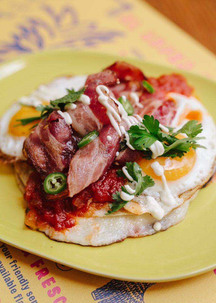 Super Rancheros Eggs sunny side up served on a corn tortilla with bacon, ham, cheese & fresh tomato salsa