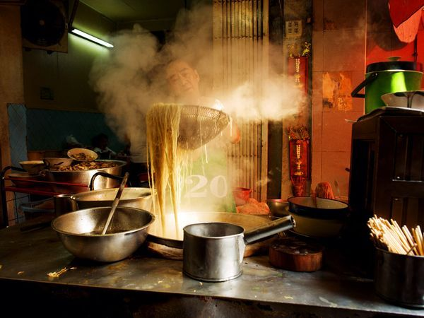 Noodles, Thailand  A strainer full of noodles, fresh off an open fire, commands the total concentration of a cook in Bangkok's Chinatown. The skill of such street chefs, and the aroma of their creations, proves irresistible to many passersby.