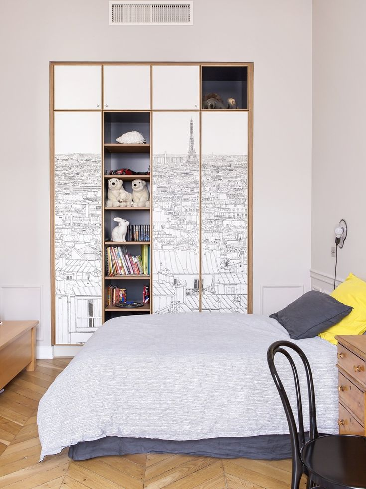 In one of the children's bedrooms, the architect built the clothes closet into the wall and clad it in Paris print wallpaper from Oh My Wall. The cabinet niches are painted in Off Black from Farrow & Ball; the walls are painted in Cornforth White.