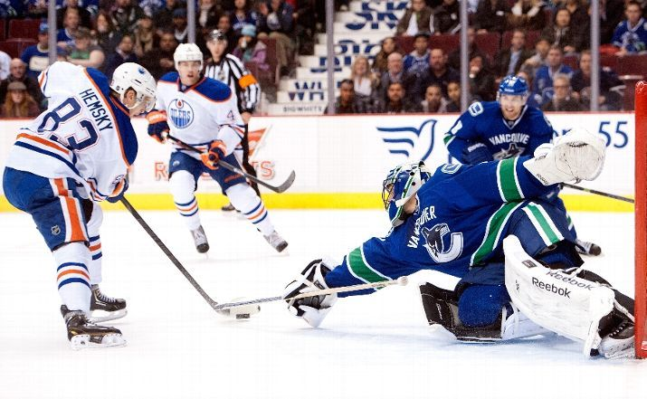 Goalie Roberto Luongo of the Vancouver Canucks reaches out to poke check the puck away from Ales Hemsky of the Edmonton Oilers  12-13-13