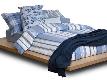 letto matrimoniale con copripiumino a righe sui toni dl blu e cuscini abbianti, coperta blu scuro
