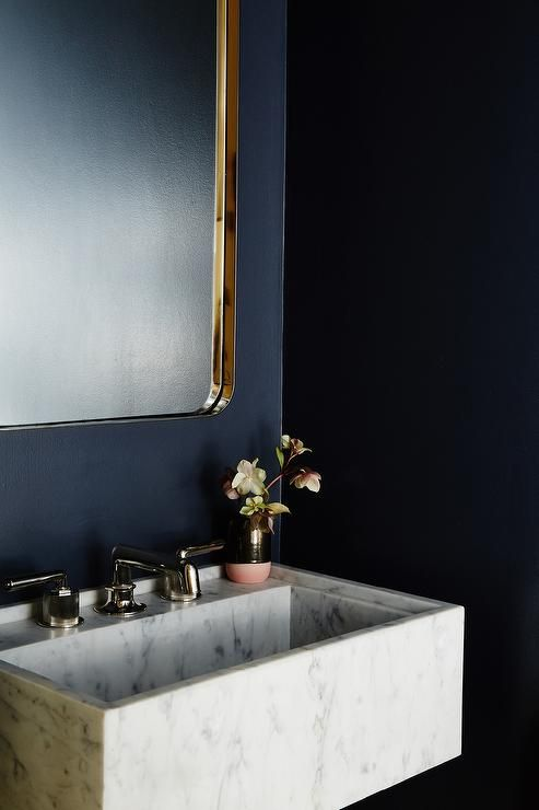 Chic dark blue powder room features a marble wall mounted sink finished with a polished brass faucet kit mounted beneath a Restoration Hardware Bristol Flat Mirror fixed to a dark navy blue painted wall.
