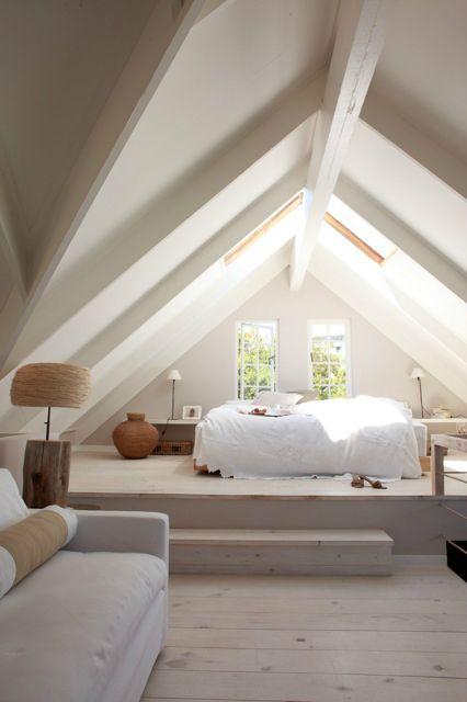 Une grande chambre simple, sous les toits, en blanc et beige.