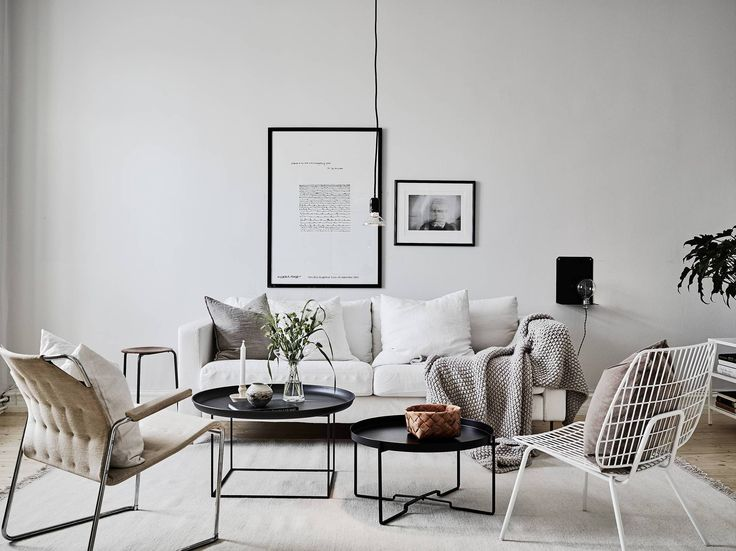 A light, calm Scandi-style living room with monochrome touches. A pale coloured sofa is offset with low black coffee tables, mismatched chairs and natural textures for a relaxed look and feel. Love MENU's string chair!