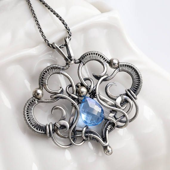 The pendant was handcrafted from 99.9% Fine silver wire that was shaped, hammered, filed, and woven together into a delicate tiny pendant. In the heart of the design is a beautiful faceted Swiss Blue Topaz. The pendant hangs from an 18 inch sterling silver chain. Let me know if you would like a different length. The jewelry was antiqued then polished to accentuate the details found in the wire woven design. All the jewelry in my shop are my own design and crafted by me. I take great joy ...