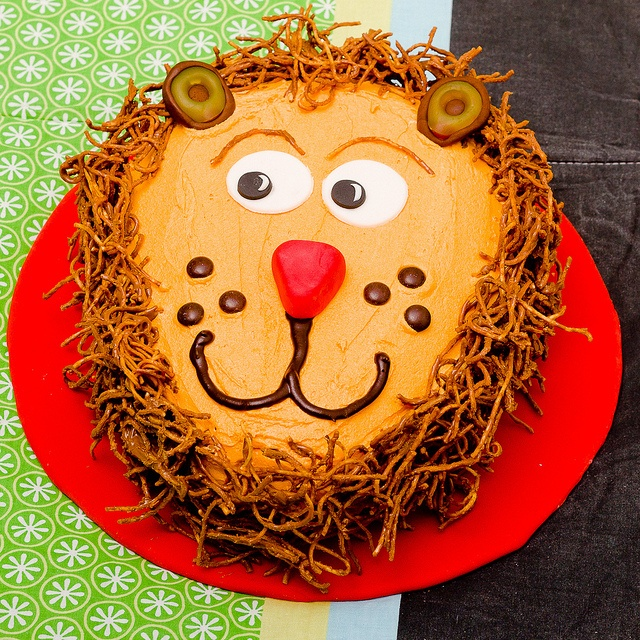 A Vanilla Lion Cake with orange buttercream frosting, piped chocolate features, and delicious peanut butter and milk chocolate dipped fried noodle for the mane.