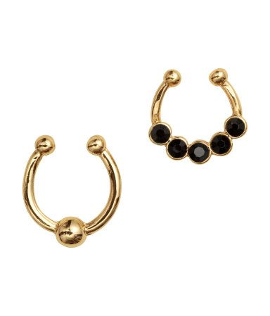 Gold-colored. Nose rings in gold-colored metal for wear on unpierced noses. One ring decorated with faceted glass beads. Adjustable size.