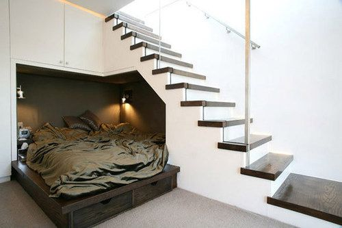 Bed in a nook underneath the stairs