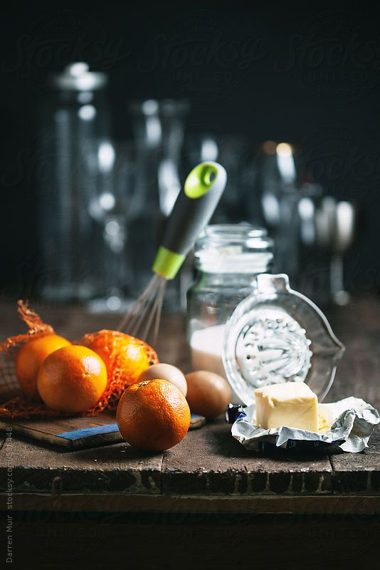 Oranges and other ingredients for making orange curd on kitchen table. by Darren Muir.Available to licence on stocksy. DARRENMUIR20 for 20% discount on checkout. #discount #code #stocksy #stock #photography #Seville #orange #curd #dark
