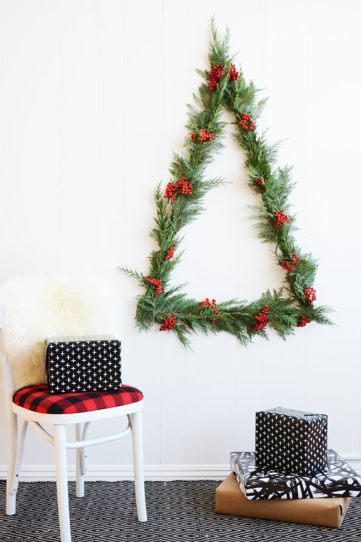 Bringing the holiday cheer with this statement wall Christmas tree DIY. Check out how to make the instillation with a few of our tools, greenery and berries. Perfect for small spaces. #fiskars #smallspacediy #christmas #christmastree