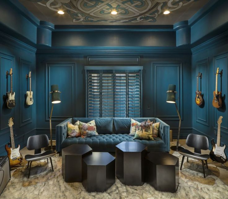 This glamorous dark teal media room was completed by imi design luxeaz