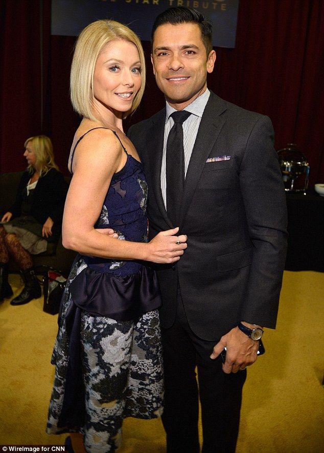 Loved up: Kelly Ripa cosied up to husband Mark Consuelos...