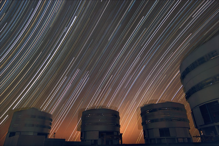 The rotating sky above ESO's Very Large Telescope at Paranal. This long exposure shows the stars rotating around the southern (left) and northern (right) celestial poles, the celestial equator being in the middle of the photo — where the stars seem to move in a straight line. The motion of the VLT's enclosures are also visible