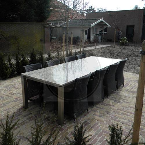 Licht gekleurde granieten tafel met donkere stoelen