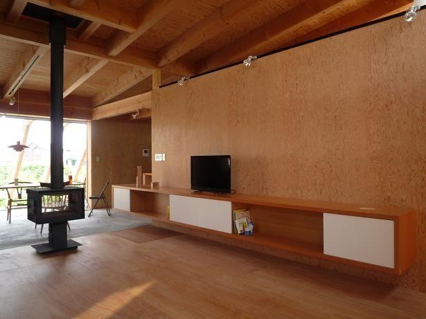 内装壁はすべて針葉樹合板で、コストを抑えながら構造的にも強化しています。天井は片流れ屋根の形状のままに構造材をあらわしにして木の温もりと経年変化を楽しみます。家の中央に置かれた薪ストーブは両面ガラス仕様でダイニング側からも炎が楽しめます。 専門家:小磯一雄|KAZ建築研究室が手掛けた、木の温もりを感じるリビング(群馬県太田市・芝屋根住宅-1|mat house)の詳細ページ。新築戸建、リフォーム、リノベーションの事例多数、SUVACO(スバコ)