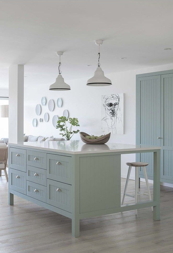 Duck egg blue oversized kitchen island shaker cabinetry with panelling and matt silver/chrome handles; white stone benchtop; white industrial pendant lights; pale timber floorboards