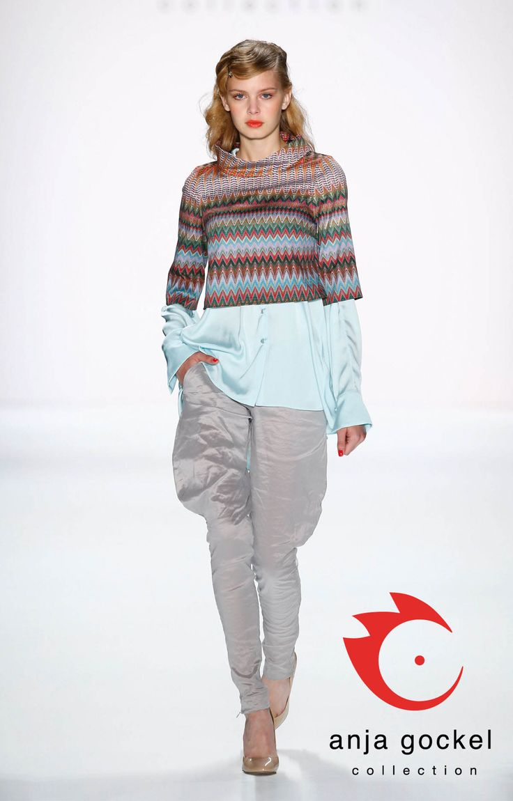 "Layering ""on fleek"". Anja Gockel`s modern interpretation of equestrian-style pants in silky grey matched by a turquoise silken long-blouse layered with a colorful, cropped pattern-sweater ."
