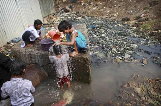 Children wash clothes and bathe at a water pipeline surrounded by sewage in Mumbai, India on Wednesday, Nov. 18.  Children of the World (25 pics + text)