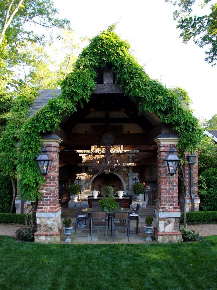 This attractive garden space by Kenny Collins features a weathered gate set in a brick wall, a brick pavilion with wisteria growing along the roof peaks and a brick water fountain structure. Large lantern-style light fixtures add to the classic feel of the space.