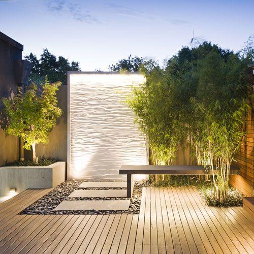 Un Jardin Sec, Terrasse Bois, Bac en béton sur une Terrasse Bois et de Pas Japonais avec une vue directe sur le Mur d'Eau.: