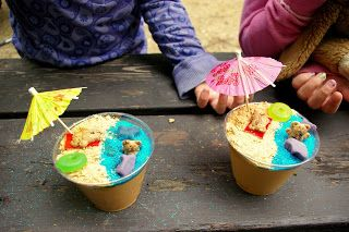 Beach Cups. -- I created mine by using homemade Vanilla Pudding, Nilla Wafers, Blue Sugar Sprinkles, Fruit Strips, Teddy Grahms, & Swedish Fish. Don't forget about the umbrella! So cute & appreciate for a Beach Party!