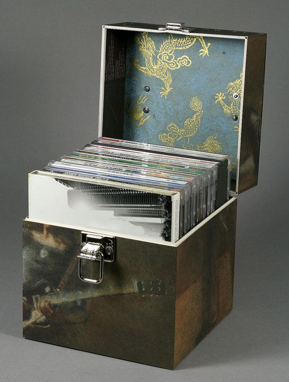 This handmade box was designed to hold 12 standard CD jewel cases - but it could contain whatever else you may want to store or take with you. Enjoy the irony of carrying your favorite digital media in an entirely analog container!  Made from one complete LP sleeve with the front cover on the outside, back cover on the inside and the vinyl record on top. Top and bottom are lined with a beautiful blue handmade imported paper printed with gold dragons and blue smoke. Black plastic handle…