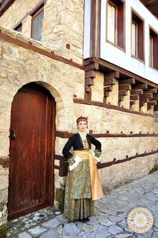 Macedonian Woman, traditional Dress outside of a traditional Macedonian home.  Edessa, Historical Macedonia, northern Greece