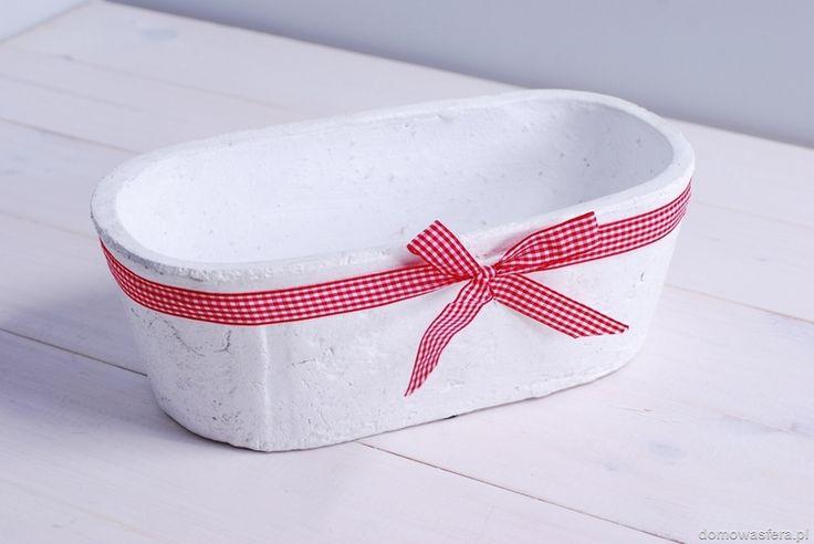 Biała osłonka na 2 doniczki bądź do użycia jako jedna większa doniczka, wykonana z materiału ciężkiego i szorstkiego. Całość została przyozdobiona czerwoną wstążką w białą kratkę.