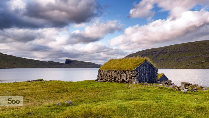 """Traditional stacked stone house with sod roof at the """"Leitisvatn"""" lake in the Faroe Islands. In earlier years the houses where used to store peat, now they are used for storing farm/boat equipment. In the background you can see the cliff """"Trælanipan"""""""