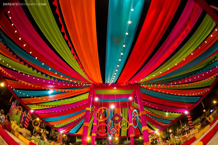 Indian wedding backdrop ideas. Colorful. Mela themed. Colorful woollen thread hanging for the wedding. Mehndi decor. Vibrant and thela for rajasthani theme. Indian street food #indian_decor_mehndi