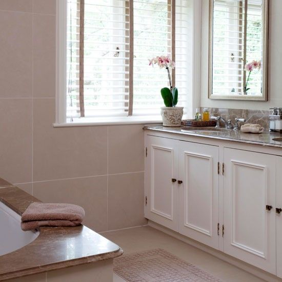 natural marble or limestone with light coloured cabinets and venetian blinds give a light and spacious feel