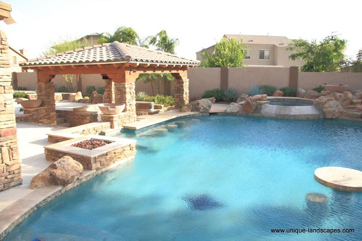 Stacked stone accents and a swim-up bar in this ramada, or Southwest shade structure. I can just imagine swimming up for a cocktail. . . Design by Unique Landscapes by Griffin of Arizona.