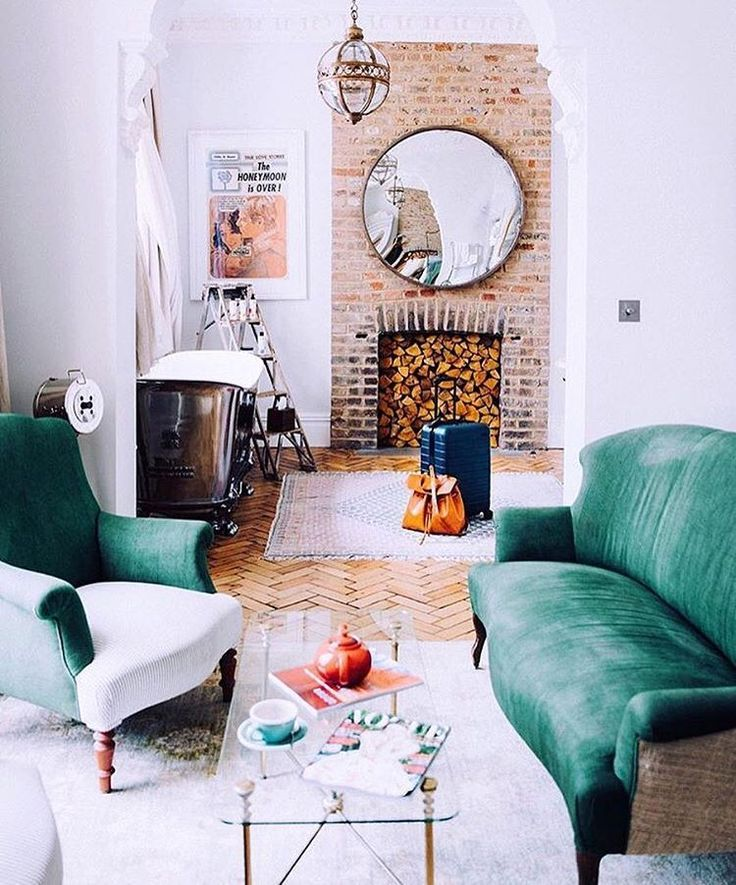 Green sofa, white walls, exposed   floorboards. Interior design. Boho bohemian living room