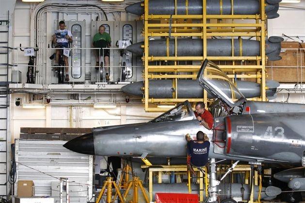 Mechanicy w hangarze francuskiego lotniskowca 'Charles de Gaulle' przygotowują samoloty do misji NATO nad Libią, 28 marca. Fot. BENOIT TESSIER/REUTERS/forum