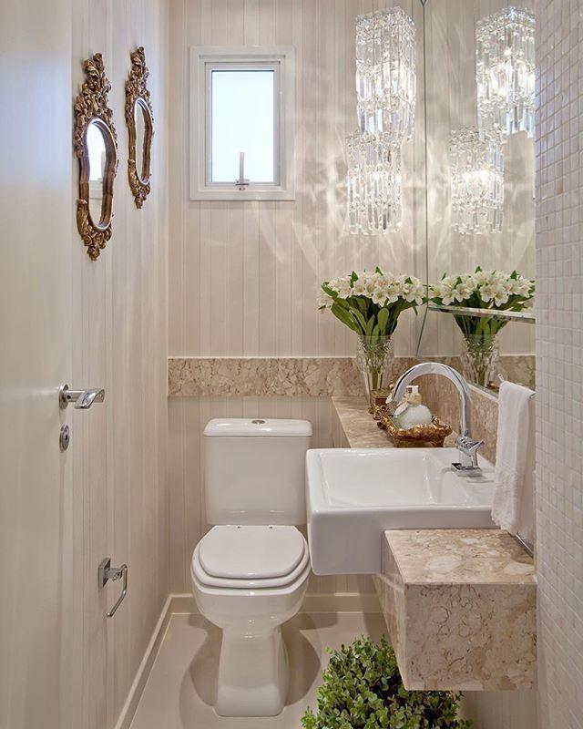 Lavabo clarinho com lustres de cristal e papel de parede listrado