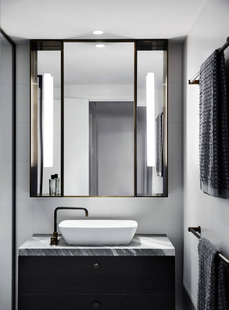 Consider removing current mirror and lighting and include larger mirror with lights on the side. Re-use current mirror (after refurb) in another area. M Residence by Studio Tate