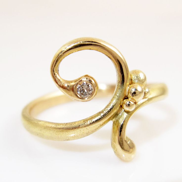 Slender 14 k gold ring, which smoothes itself around your finger, playfully ending in a curl. Here a 0,02 champagne colored diamond glitters up at you, while winking at the playfull bubbles connecting the two halves of the ring.