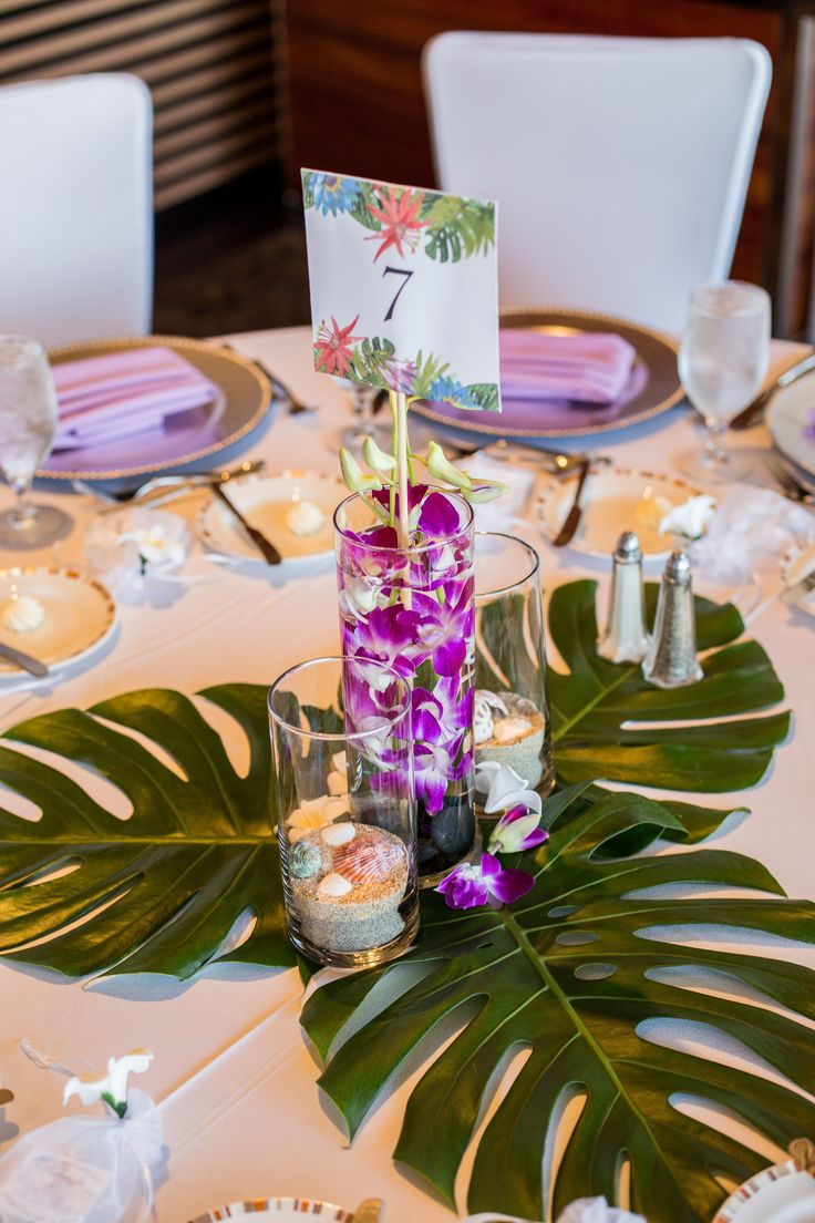 One of our tropical centerpieces with monstera leaves. The other tables alternated between monstera and palm leaves.