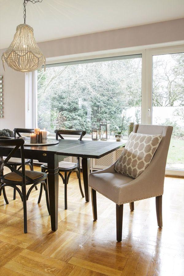 Das Zusammenspiel verschiedener Stühle verleiht dem Esszimmer eine individuelle Note. Zwei gepolsterte Sessel an den Kopfenden machen den Raum gemütlicher und sorgen für eine ausgewogene Symmetrie. Die passenden grafischen Kissen spiegeln die Wandfarbe wider.