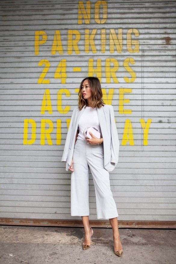 Aimee Song wears a white top, gray draped blazer, culottes, metallic pointed-toe pumps, and a white clutch