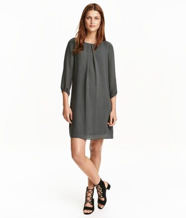 Dark gray. Straight-cut chiffon dress with box pleat at front, 3/4-length sleeves, and visible zip at back of neck. Jersey lining.