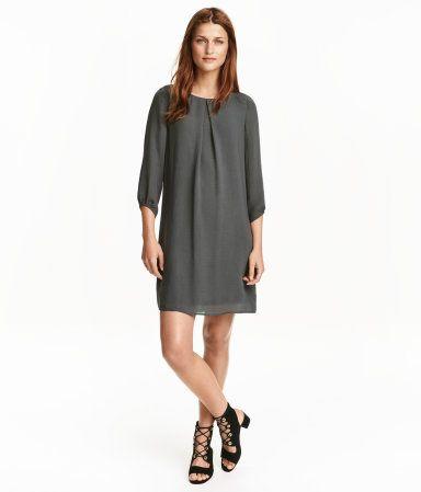 Mørk grå. En rett skåret kjole i chiffon. Kjolen har fold foran og trekvartlange ermer. Synlig glidelås i nakken. Trikotfôret.