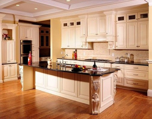 Cream colored kitchen cabinets with black granite top island and