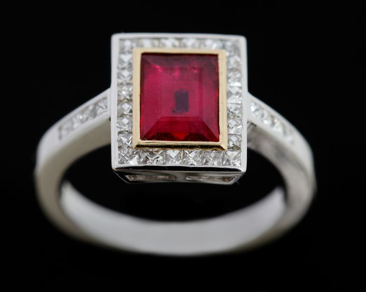 An intense Ruby surrounded by French cut Diamonds in 18 carat white gold