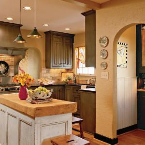 Cottage Style #Kitchen | Buttery-beige walls are a nice complement to the slate green cabinets. The pairing makes the entire kitchen feel warm and cozy.