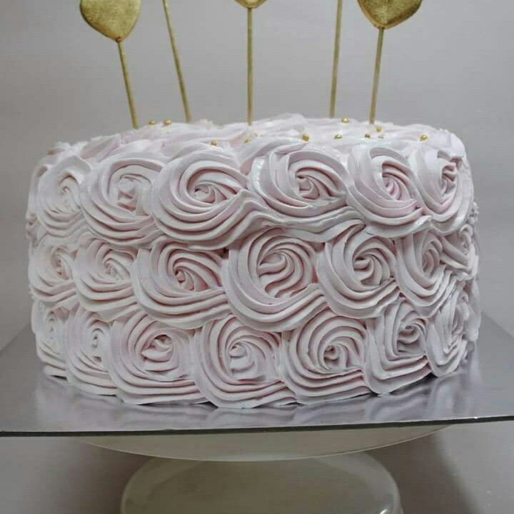Wedding cake with swirled frosting roses and gold hearts