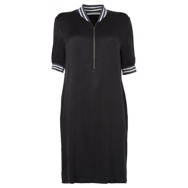Halflange jurk gemaakt van zijdezacht cupro die losjes om het lichaam valt. De jurk heeft een sportieve taping van geribde stof bij de kraag en mouwen en heeft een v-hals en rits aan de voorkant. Een echt sportief, maar vrouwelijk jurkje door de details en de stof.