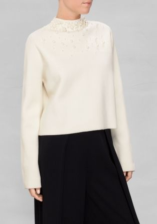 Sturdy, yet soft wool quality and elaborate pearl embellishement charm this sophisticated mock turtleneck sweater with a boxy, cropped fit.