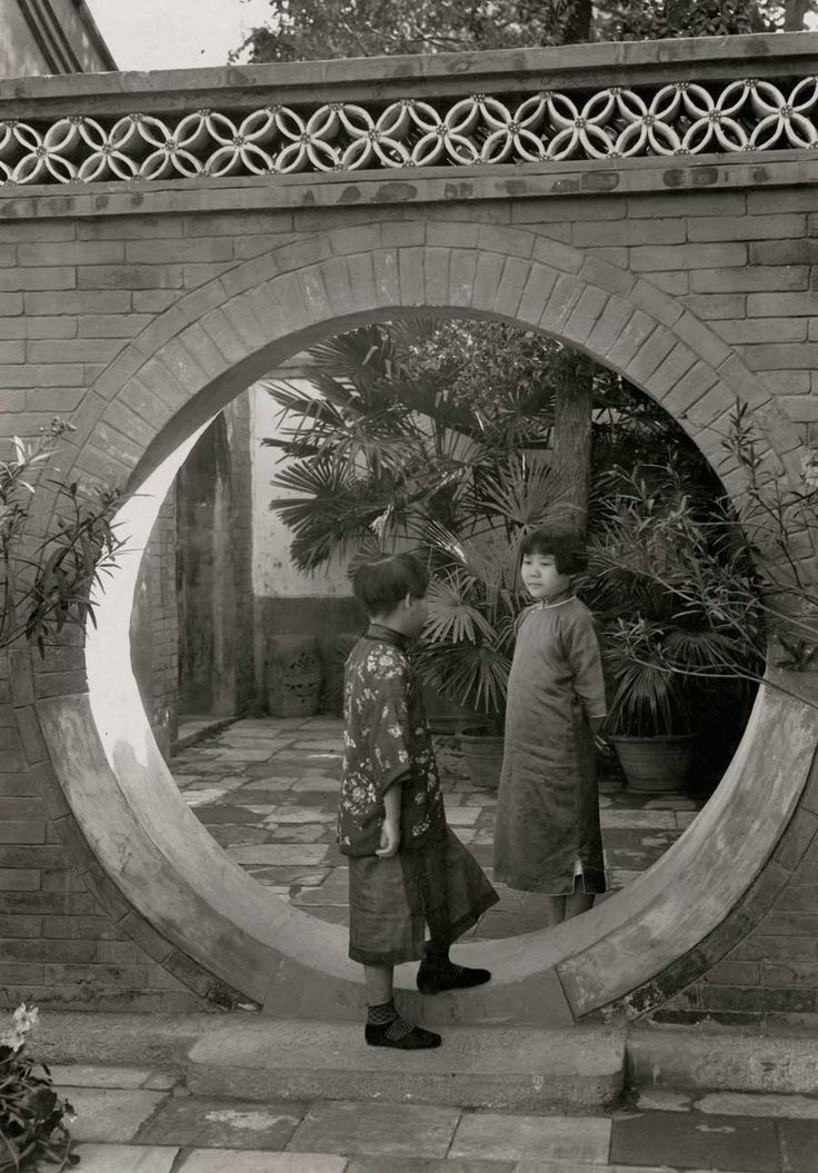 Two young Chinese girls chat with each other in a moon gate in a courtyard of a Chinese home, 1932.